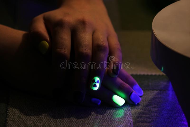 The original manicure in the form of a radioactive danger sign with gel shellac varnish, glows in the dark with. Ultraviolet light stock photos