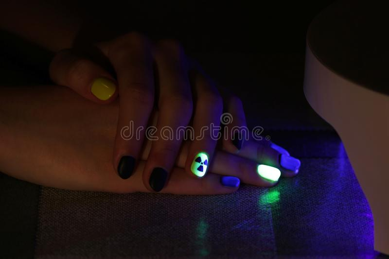 The original manicure in the form of a radioactive danger sign with gel shellac varnish, glows in the dark with. Ultraviolet light stock image