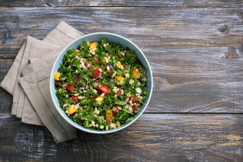 Original oriental salad tabbouleh with cabbage cale, parsley, bulgur, tomatoes and red onions on a wooden table. Top view, free space. healthy homemade food royalty free stock images
