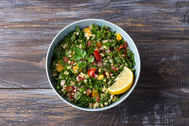 Original oriental salad tabbouleh with cabbage cale, parsley, bulgur, tomatoes and red onions on wooden table. Top view. healthy homemade food royalty free stock images