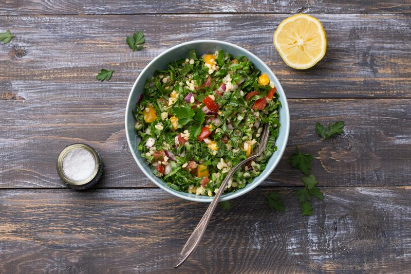 Original oriental salad tabbouleh with cabbage kale, parsley, bulgur, tomatoes and red onions on a wooden table. Top view. healthy homemade food royalty free stock photo