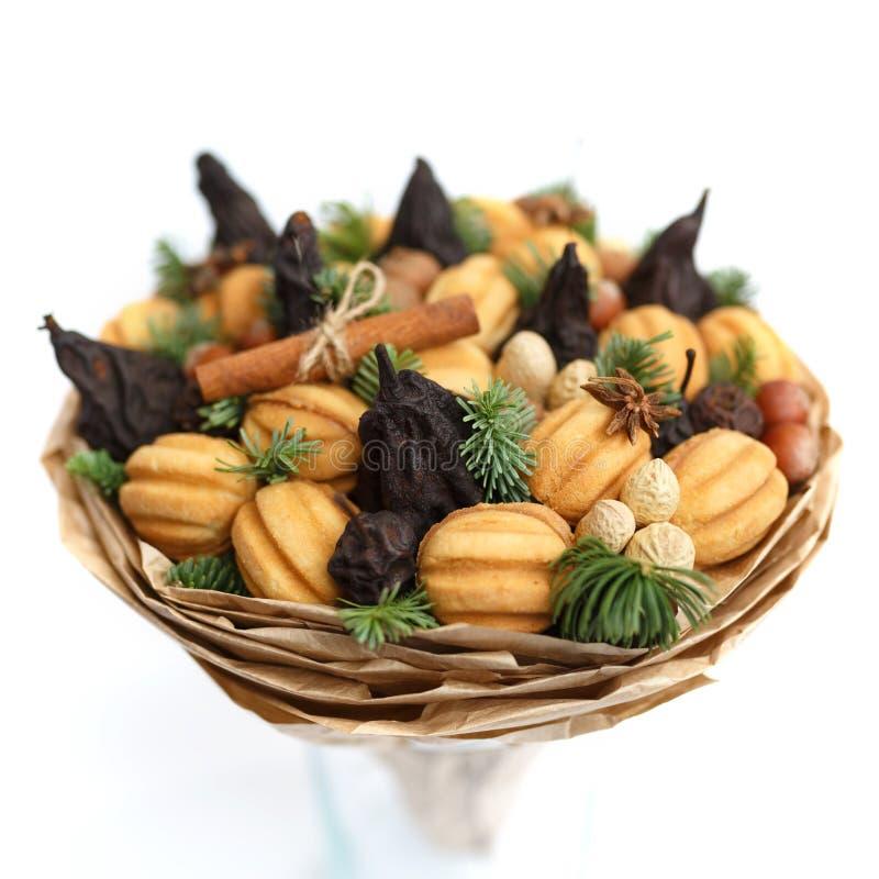 Original- söt gåva i form av en bukett som består av torkade frukter, kakor, muttrar på en vit bakgrund royaltyfri foto