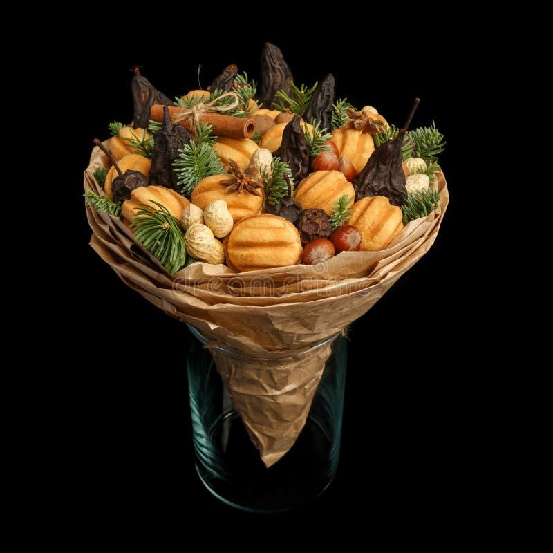 Original- söt gåva i form av en bukett som består av torkade frukter, kakor och muttrar som står i en exponeringsglasvas på en sv arkivfoto