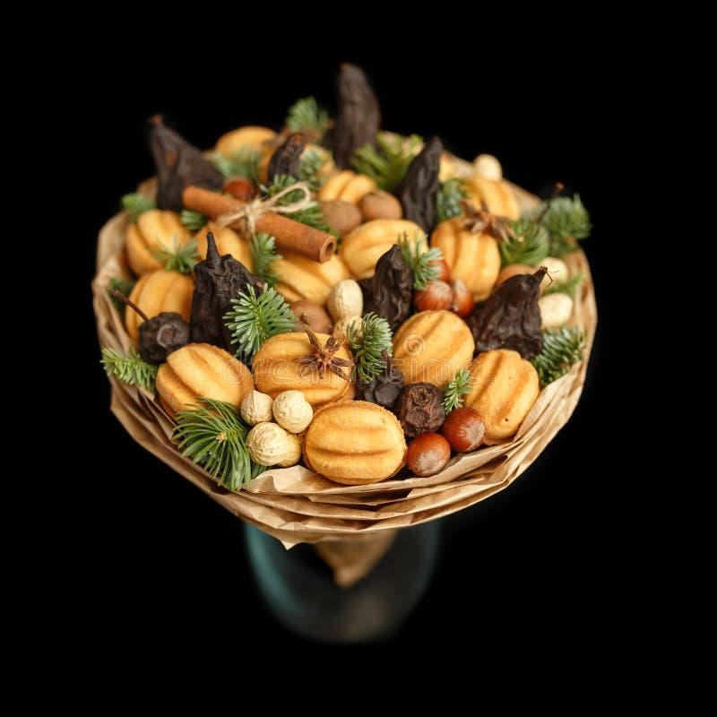 Original- söt gåva i form av en bukett som består av torkade frukter, kakor och muttrar som står i en exponeringsglasvas på en sv arkivbilder