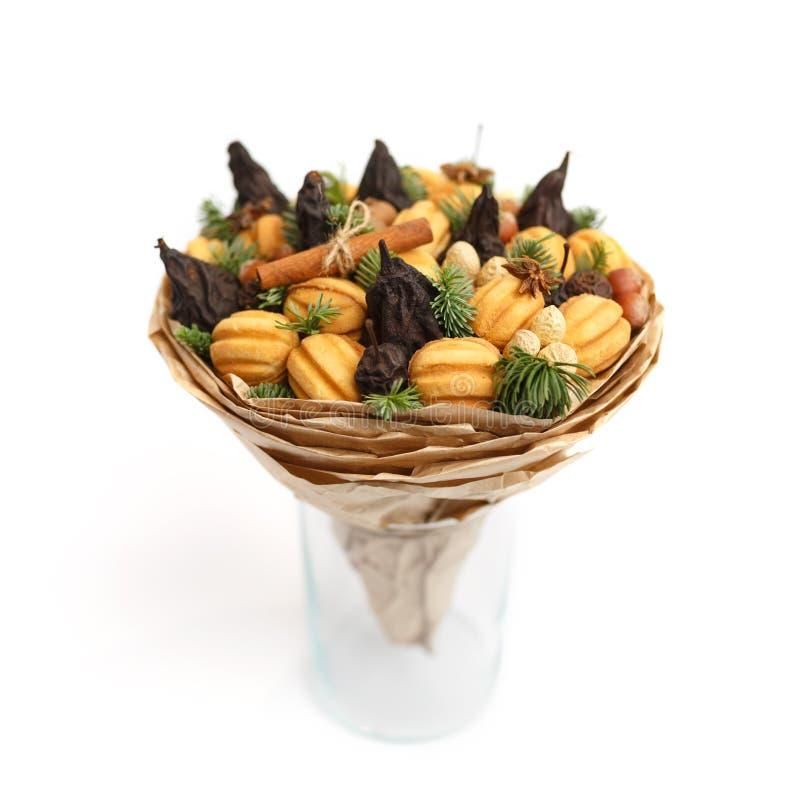 Original- söt gåva i form av en bukett som består av torkade frukter, kakor och muttrar som står i en exponeringsglasvas på en vi royaltyfri fotografi