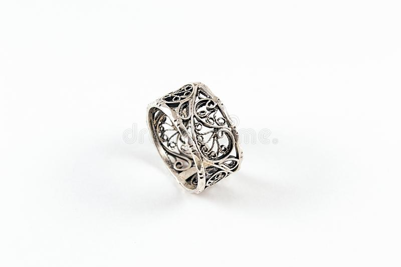 Silver Filigree Ring. Original silver ring crafted by skilful jeweller and a mighty goldsmith. Grey, shiny silver on white background. Ancient filigree technics stock photos