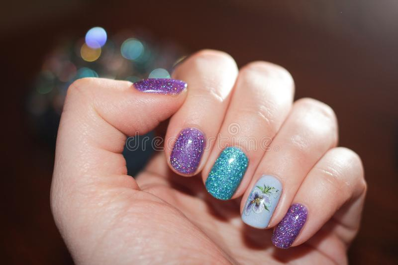 Original spring nail design. Forget-me-not flower pattern on nails - sticker stock photo