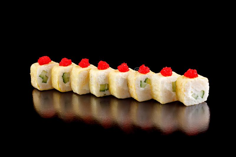 Original sushi rolls in an omelette with cream cheese and cucumber on a black background. stock photography