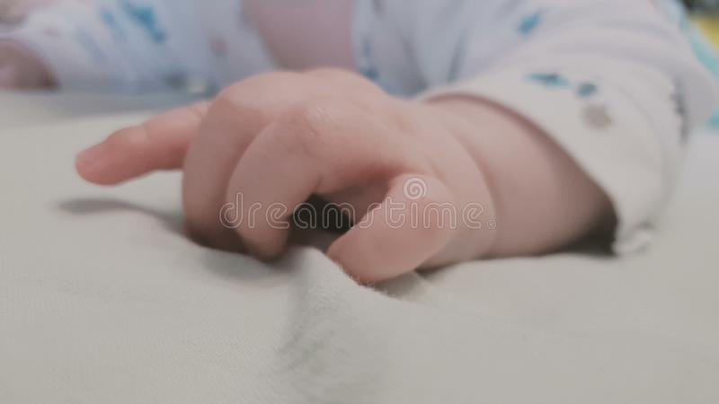 Tiny hand of a small baby lying on a bed and fidgeting royalty free stock image