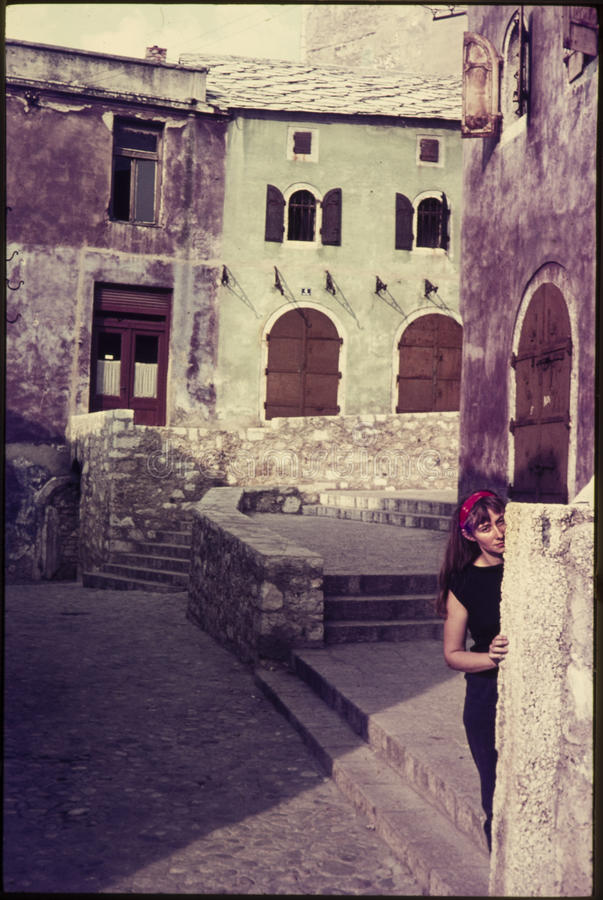 Original vintage colour slide from 1960s, young woman hiding behind a wall. royalty free stock photos