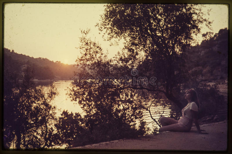 Original vintage colour slide from 1960s, young woman sitting by royalty free stock image