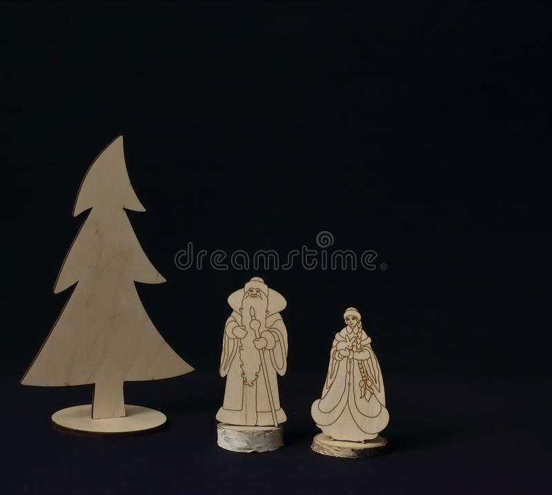 Original vintage wooden figures of Santa Claus and Snow Maiden near Christmas tree on black background. Symbolic concept - stock images