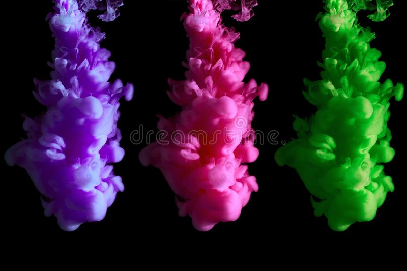 Original visualization of trend colors in 2018: UFO green, Plastic pink, proton purple, paint stream in water, abstract background royalty free stock photo