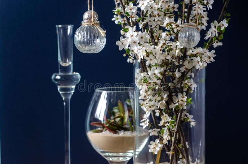 Original wedding flower decorations in the form of mini-vases and bouquets of flowers, hanging on a flowering branch royalty free stock photo