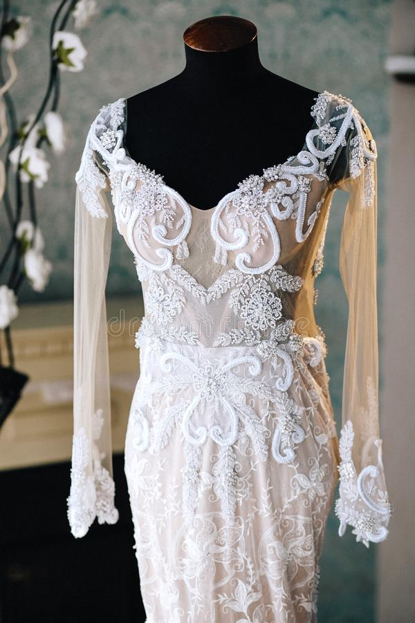 Original wedding lace embroidered dress with long sleeves on a black mannequin royalty free stock photography