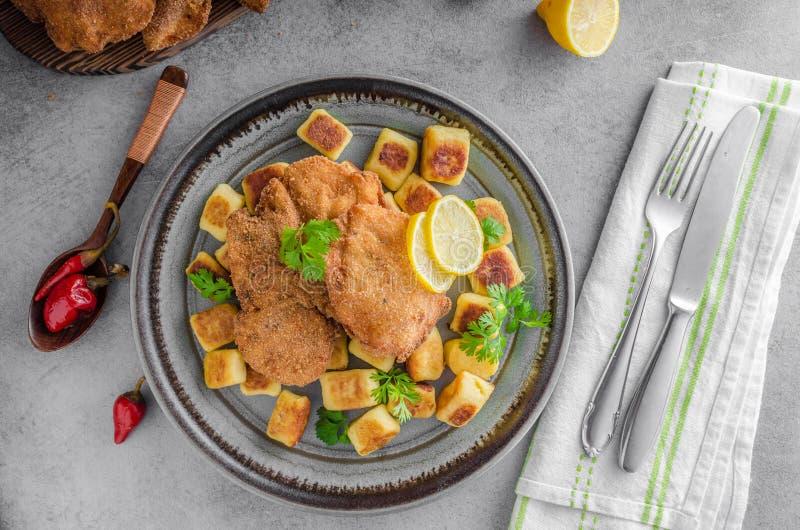 Originale della cotoletta con il limone e gnocchi fritti immagine stock