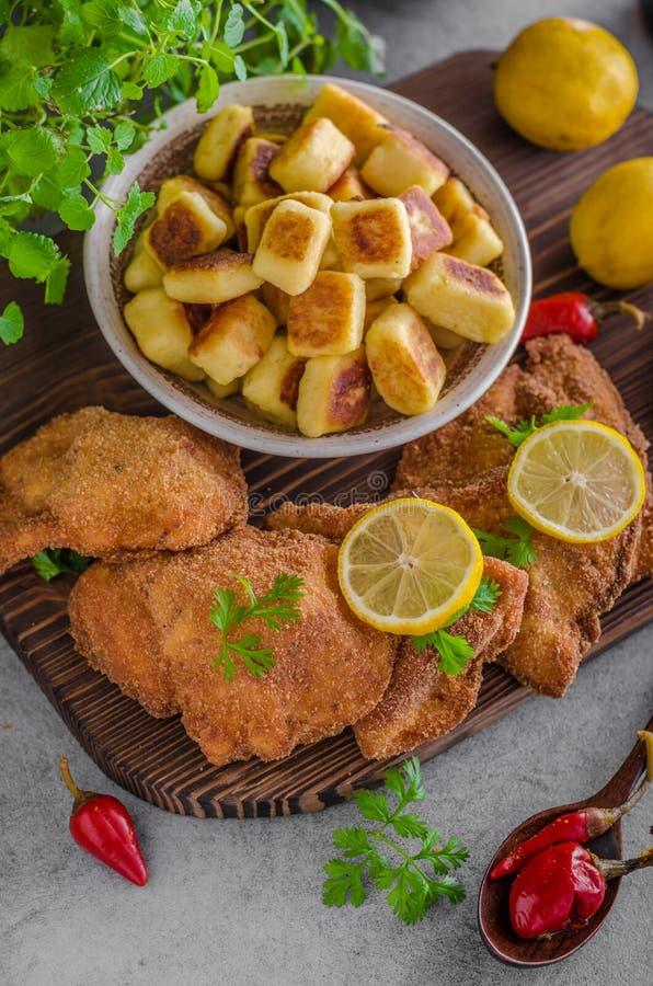 Originale della cotoletta con il limone e gnocchi fritti immagini stock libere da diritti