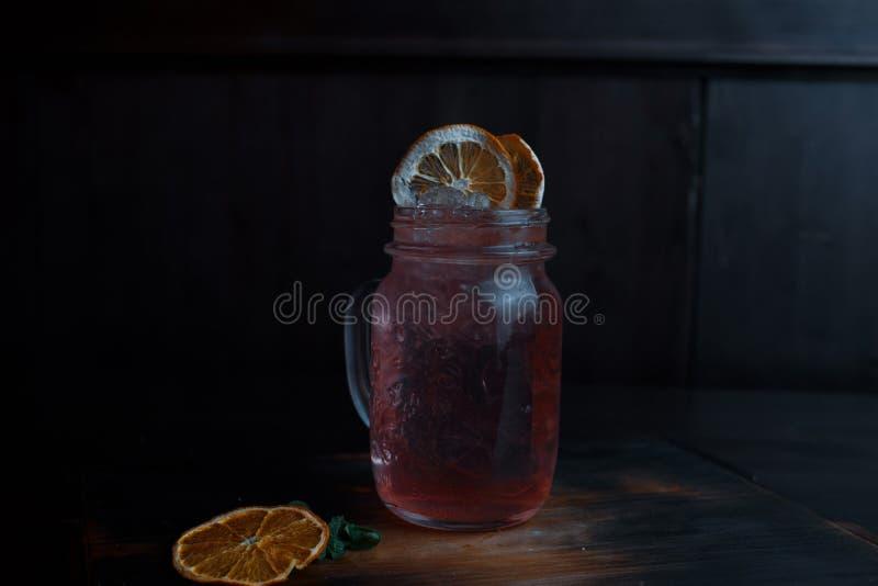 Originele alcoholische roze die cocktail met tequila en wodka met frambozenstroop, met droge en verse oranje plakken wordt verfra royalty-vrije stock fotografie