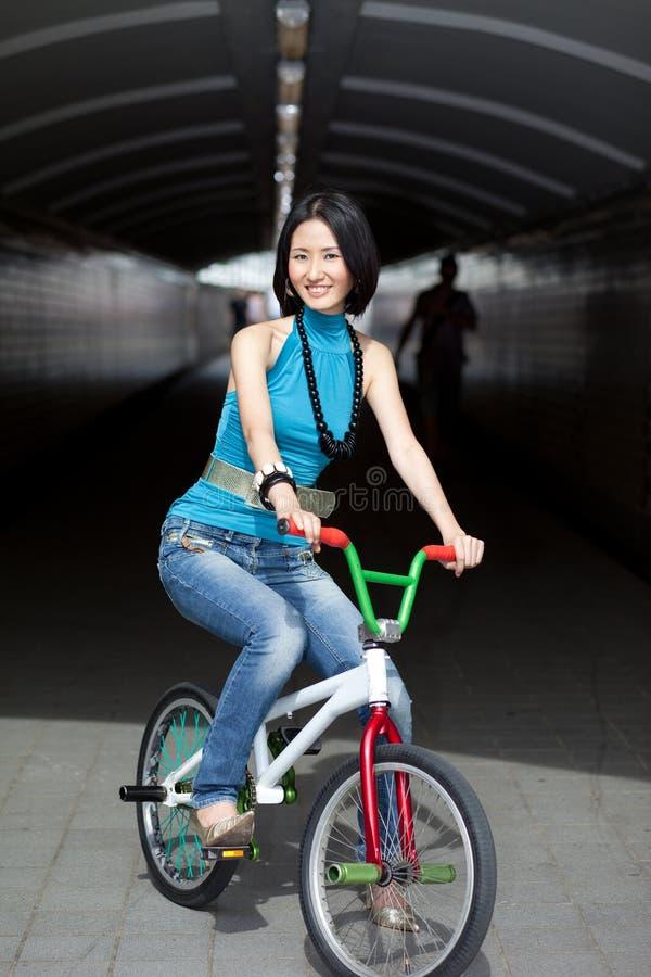 Originele, funky Chinese vrouw op straatfiets stock foto