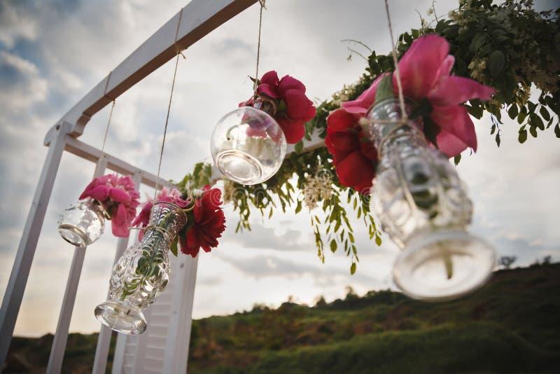 Originele huwelijks bloemendecoratie in vorm van minivazen en boeketten van bloemen die van huwelijksaltaar hangen, openluchtstra stock fotografie