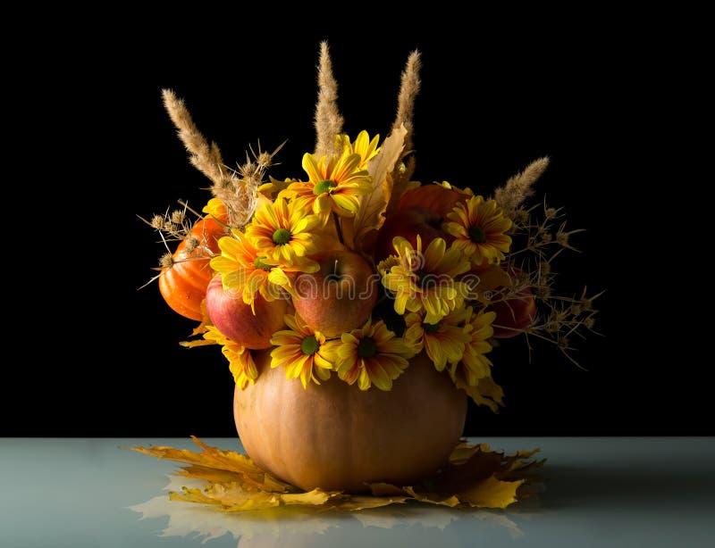 Originele pompoenvaas met vruchten en bloementribunes op de herfst l royalty-vrije stock afbeeldingen