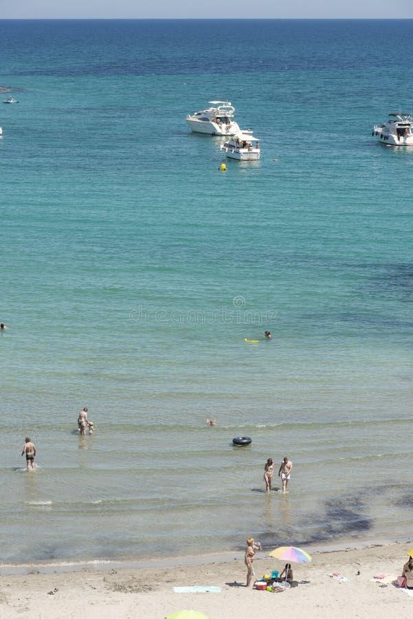 Orihuela Costa Hiszpania, Czerwiec, - 16, 2018: Ludzie sunbathing i pływa przy Cala Capitan plażą w Cabo Roig, popularny miejsce  zdjęcia royalty free