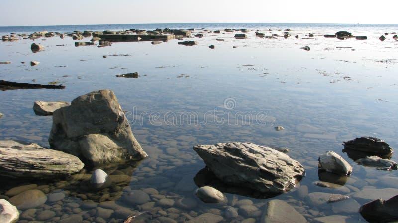 Orilla abandonada del mar, llena de la calma, rocas en el agua fotos de archivo