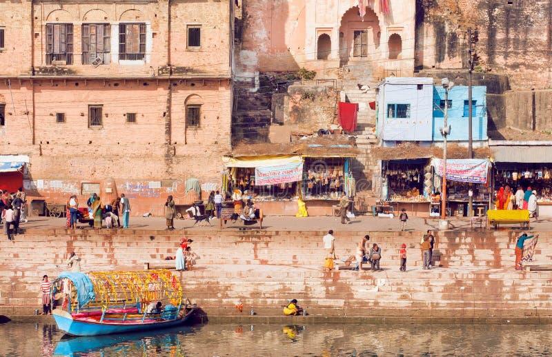 Orilla de la ciudad india con la muchedumbre de gente, de barcas y de mercados ocupados imagen de archivo