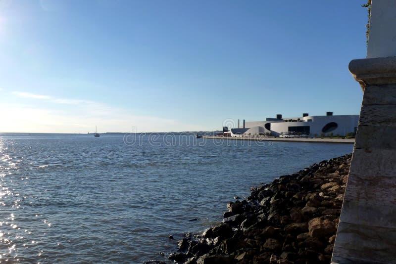 Orilla de mar rocosa de Lisboa con la agua de mar y el edificio azules del museo fotos de archivo libres de regalías