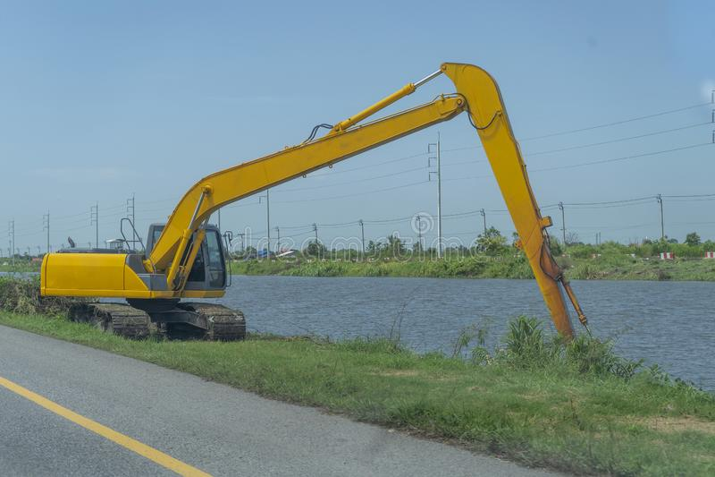 Orilla de trabajo de la retroexcavadora amarilla y en el borde de la carretera imagenes de archivo