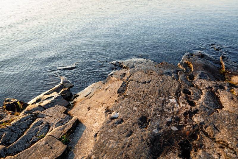 Orilla lisa del lago de la roca en el amanecer foto de archivo libre de regalías
