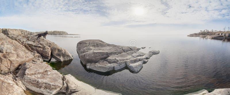 Orilla rocosa del lago en un día soleado foto de archivo