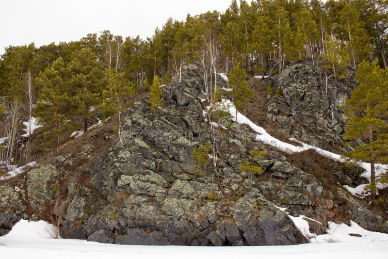 Orilla rocosa del río congelado foto de archivo