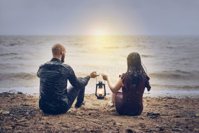 A orillas del mar, un joven pareja de hombres y mujeres al atardecer hombre y mujer mantienen la linterna juntos fotos de archivo libres de regalías