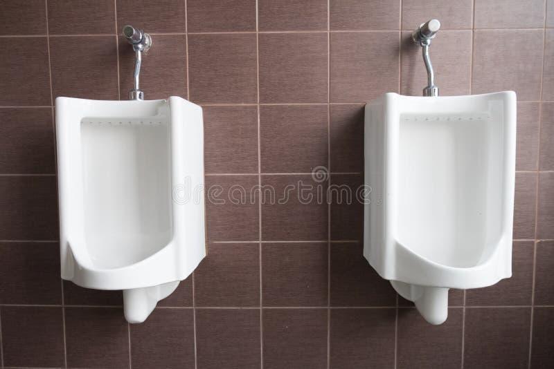 Orinali bianchi nella toilette pubblica degli uomini immagine stock
