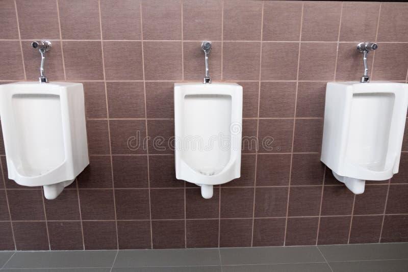 Orinali bianchi nella toilette pubblica degli uomini immagine stock libera da diritti