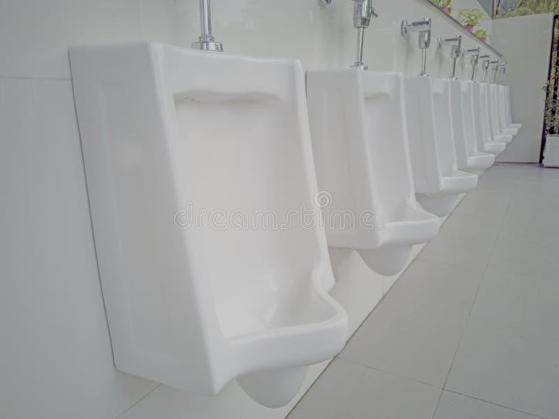 Orinali del primo piano nel bagno degli uomini, fila della toilette pubblica degli uomini all'aperto degli orinali, progettazione immagini stock