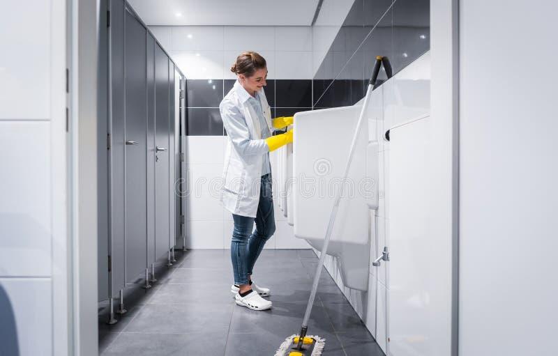 Orinali di pulizia della donna del portiere nella toilette pubblica fotografie stock