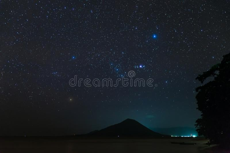 Orion constellation starry sky stars over Gunung Api volcanic island glowing in tropical night Indonesia Banda Islands Moluccas. Maluku stock photos