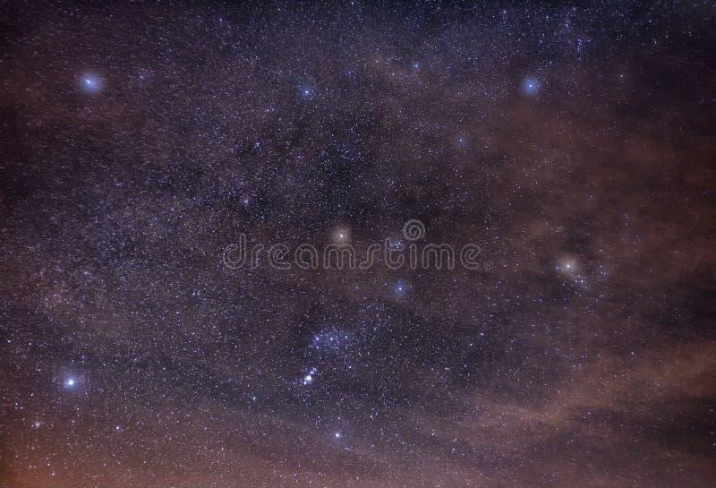 Orion med dess kosmiska grannar i molnen arkivbild