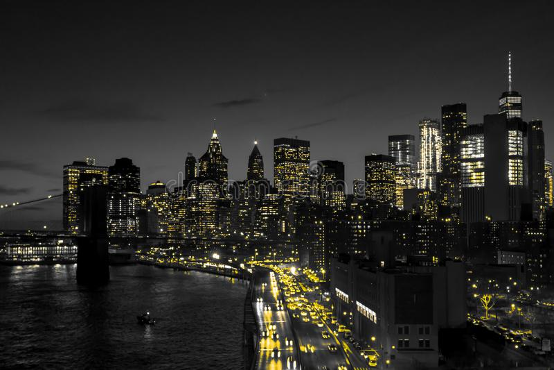 Orizzonte in bianco e nero di notte di New York con le luci gialle dorate che emettono luce in Manhattan del centro immagine stock libera da diritti