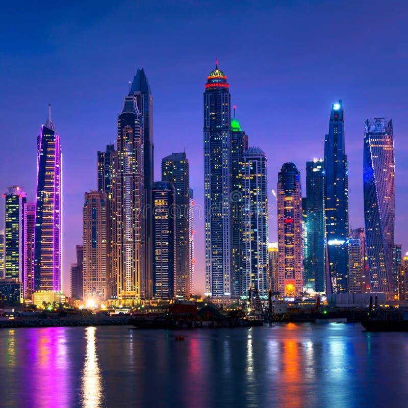 Orizzonte del porticciolo del Dubai alla notte con le riflessioni dell'acqua immagine stock