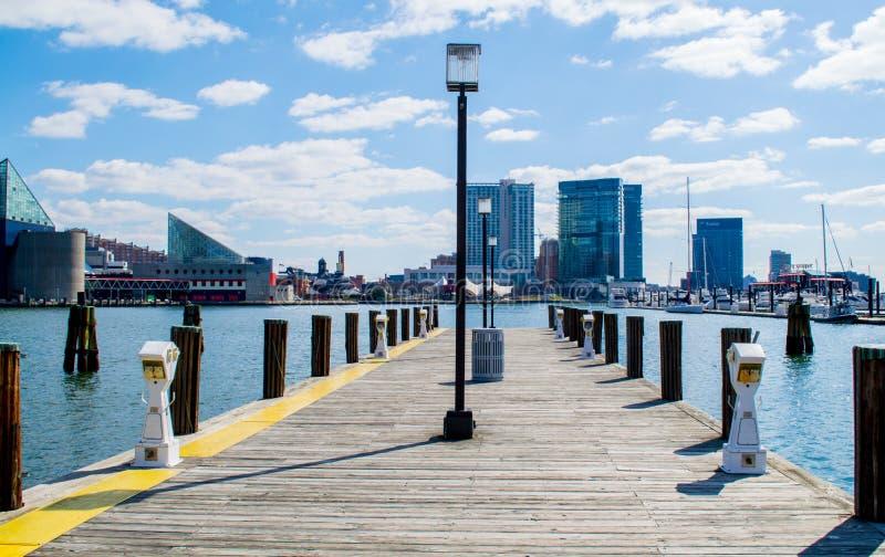 Orizzonte del porto interno del ` s di Baltimora da un pilastro di legno fotografie stock