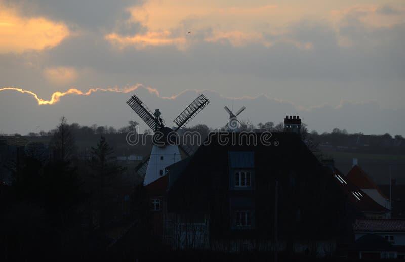 Orizzonte della città nell'uguagliare luce con due vecchi mulini a vento immagini stock