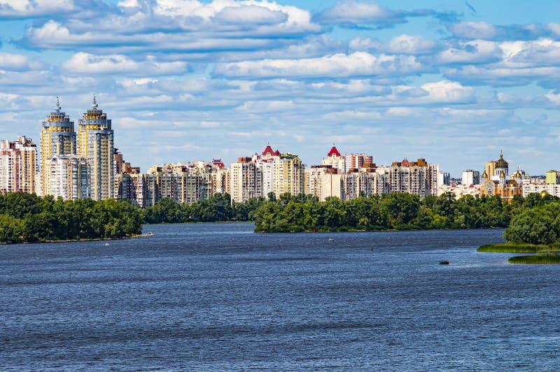 Orizzonte della città sopra il fiume contro il cielo blu fotografia stock