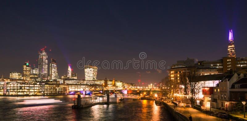 Orizzonte di Londra alla notte con il Tamigi, i ponti, le costruzioni della città e l'attraversamento dei Riverboats immagine stock libera da diritti