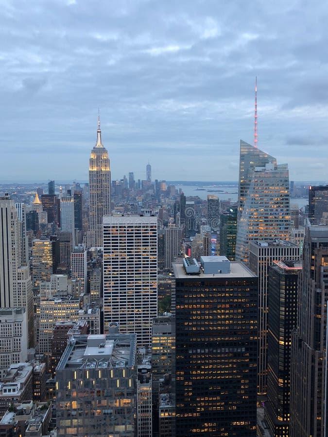 Orizzonte di Midtown di Manhattan con i grattacieli illuminati al tramonto immagine stock libera da diritti