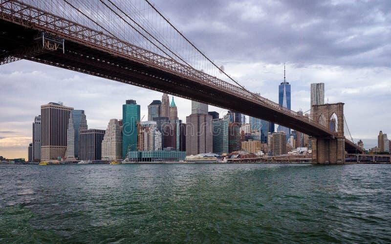 Orizzonte di New York sotto il ponte di Brooklyn fotografia stock
