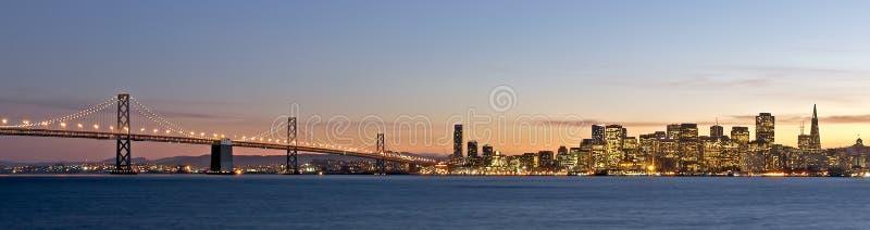 Orizzonte di San Francisco con il ponticello della baia al tramonto fotografie stock libere da diritti