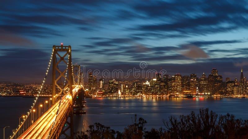 Orizzonte di San Francisco e ponte della baia alla notte fotografia stock libera da diritti